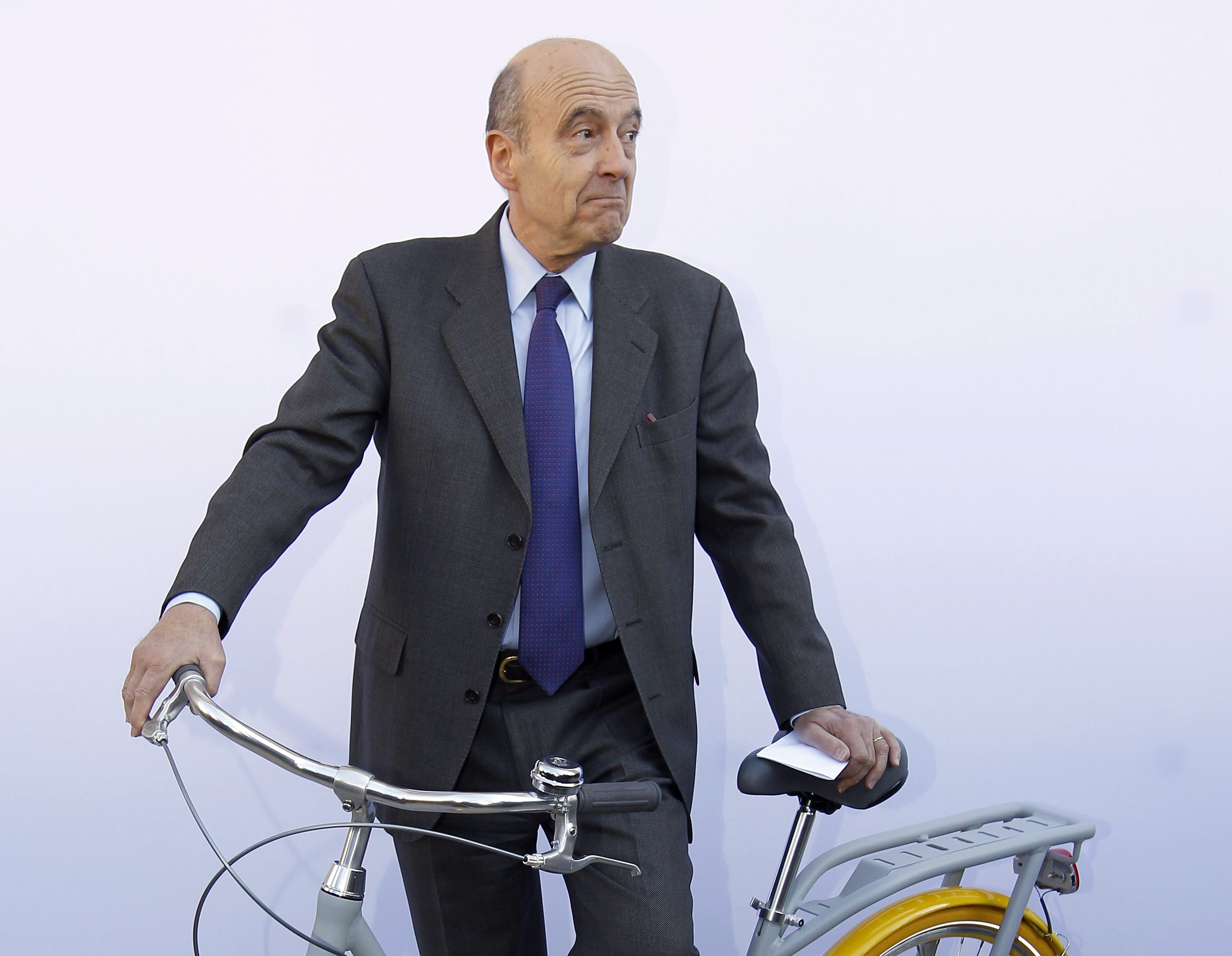 "Alain Juppe, Mayor of Bordeaux, poses with the ""Pibal"" public bicycle designed by French designer Philippe Starck during a presentation at the Bordeaux city hall February 19, 2013. The hybrid bicycle, which will be available to the public from September 2013, has a central platform allowing the rider to push it like a scooter during heavy traffic, and has fluorescent tyres for security at night. REUTERS/Regis Duvignau (FRANCE - Tags: BUSINESS SOCIETY)"