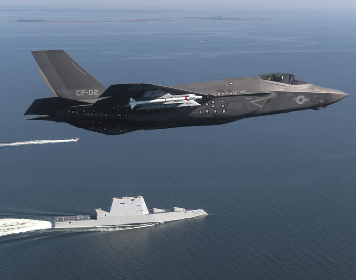 """An F-35 Lightning II Carrier Variant (CV) piloted by U.S. Marine Corps Maj. Robert """"Champ"""" Guyette II, a test pilot from the F-35 Pax River Integrated Test Force (ITF) assigned to the Salty Dogs of Air Test and Evaluation Squadron (VX) 23, flies over the stealth guided-missile destroyer USS Zumwalt (DDG 1000) as the ship transits the Chesapeake Bay on Oct. 17, 2016. USS Zumwalt, the Navy's newest and most technologically advanced surface ship, joined the fleet Oct. 15. The F-35C Lightning II — a next generation single-seat, single-engine strike fighter that incorporates stealth technologies, defensive avionics, internal and external weapons, and a revolutionary sensor fusion capability — is designed as the U.S. Navy's first-day-of-war, survivable strike fighter. The U.S. Navy anticipates declaring the F-35C combat-ready in 2018. (U.S. Navy photo by Andy Wolfe/Released)"""